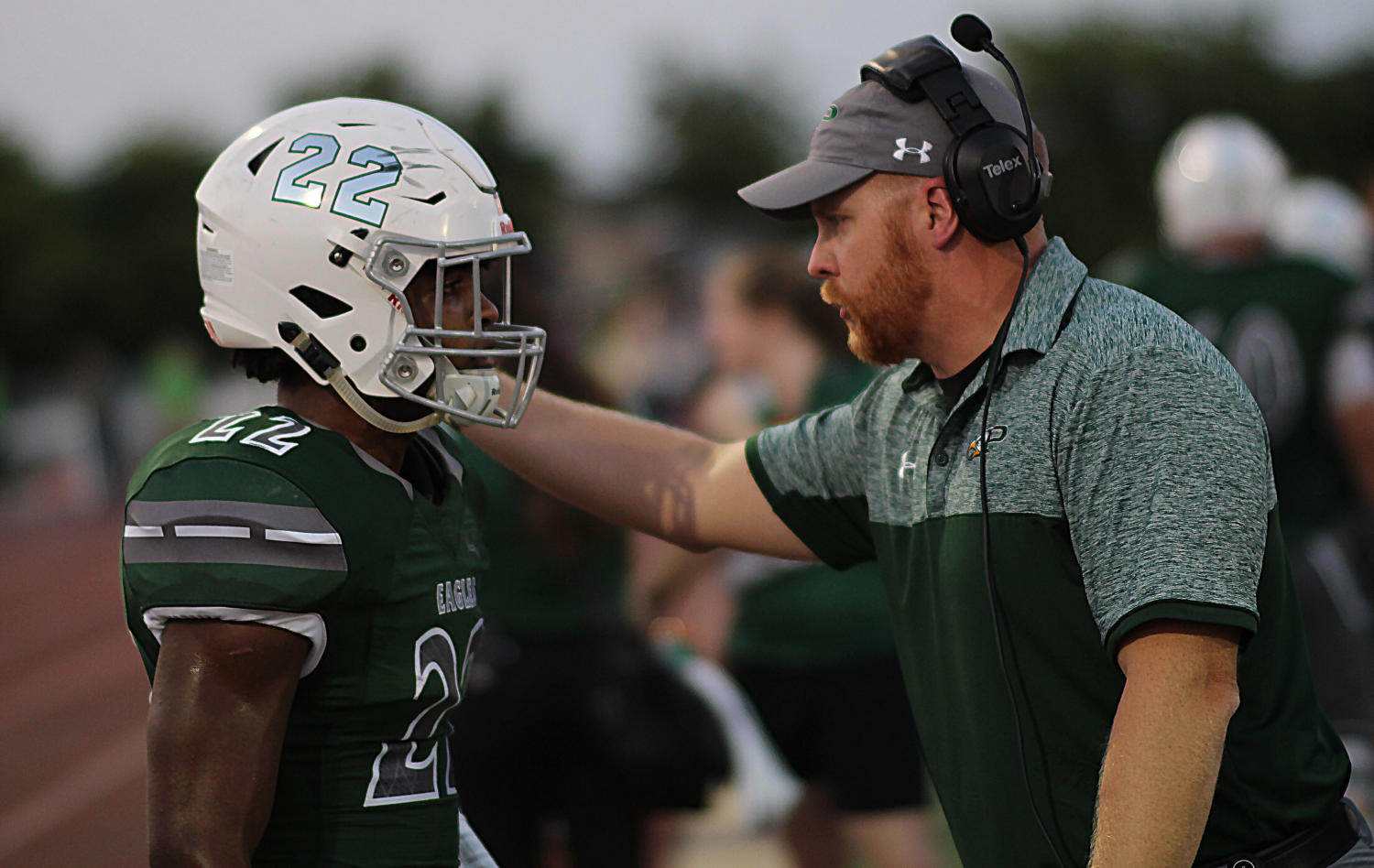 Kaleb Adams (22) talking with Coach Thompson on the sideline. Adams had a quiet night against Lake Ridge, totaling 30 yards on 13 carries.