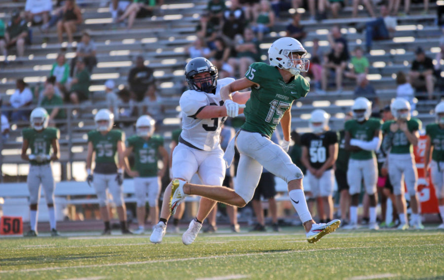 Senior Gaven Mabrey shoves off Eaton's defense as it's members try to stop him from receiving the ball. Mabrey plays quarterback and safety. This night saw Prosper play against the Eaton Eagles in a pre-season scrimmage.