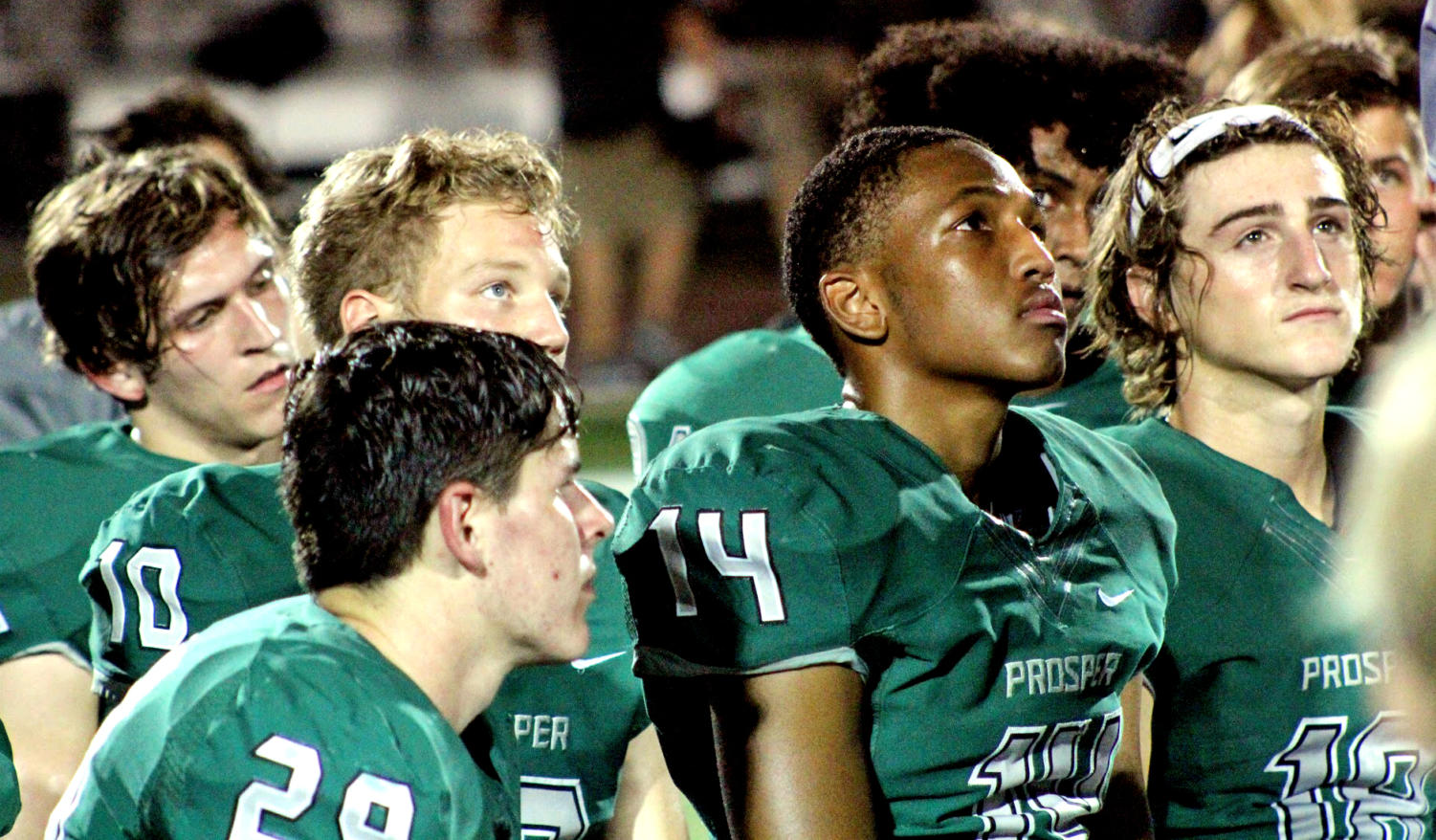 In the midst of the rest of the Eagles, Prosper players Reid Applewhite, No.  29, Lee Rowden, No. 10, Josh Graham, No. 14, and Caleb Cox, No. 10, reflect over the night as one of their coaches gives a recap after the end of the game. The boys played Eaton in this pre-season match-up. Head football coach Brandon Schmidt leads the Eagles.