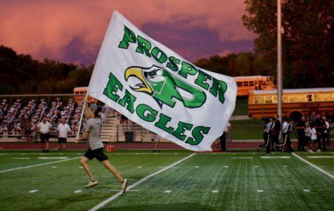 Senior Spirit Leader Nico Ray runs flag down football field