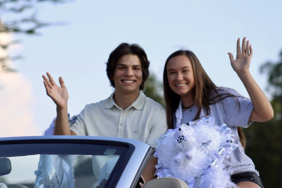 Seniors+Cole+Spurr+and+Haley+Foley+wave+at+the+crowd.+They+won+Homecoming+court+during+half+time+at+the+football+game+on+Thursday.+Foley+is+a+third-generation+homecoming+queen.+