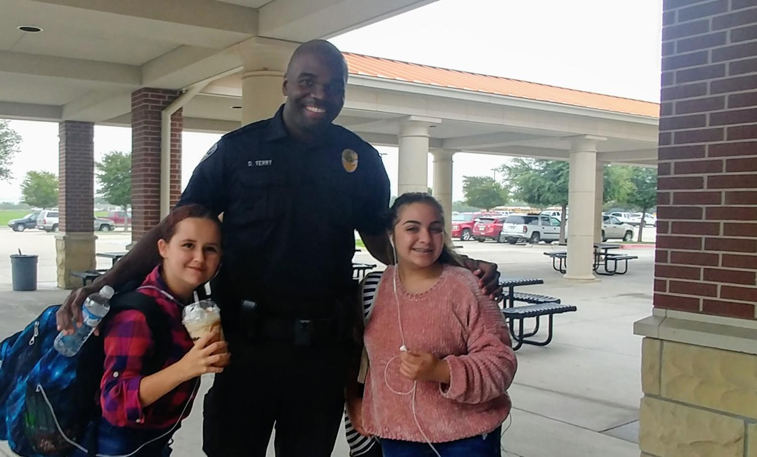 Sophomore Marissa Armont, Officer Darrell Terry and sophomore Yasmin Kazraji greet each other Wednesday, Sept. 12, at the patio entrance on the way into school.    The trio said they meet up often to talk, including how to navigate being new in a high school of more than 3,000 students.