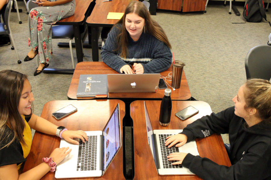"""Ana Arredondo, Sydney Washburn and Kennedy Wyles work on Macbooks in Room 1247 during second period. Due to new rules that went into effect this year, though, these students will not be printing their assignments to turn into their instructors due to new rules that prohibit students from printing throughout the school building.  """"Why are we having students print unless it is absolutely necessary?"""" principal John Burdett asked in an email sent to faculty members. """"We have unlimited storage accessible to any device with an internet connection. Save trees, and make the Lorax happy."""""""