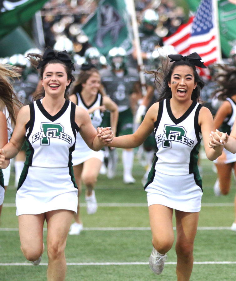 Kacey+Boston+and+Ashley+Brown+race+ahead+of+the+football+team+as+the+game+starts+September+20%2C+2018.+The+homecoming+game+is+against+McKinney+High+School.+Boston+is+an+anchor+for+Eagle+Nation+News.+