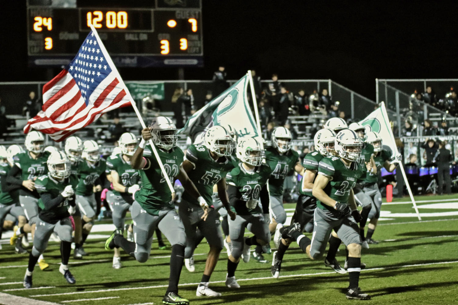Varsity senior Dylan Harrison, No. 20 in the center, helps lead his team into Eagle Stadium. Harrison will be playing in the last game at Eagle Stadium, starting at 7 p.m. Friday when Prosper takes on Plano West. His father, Jeff Harrison, played in the first.