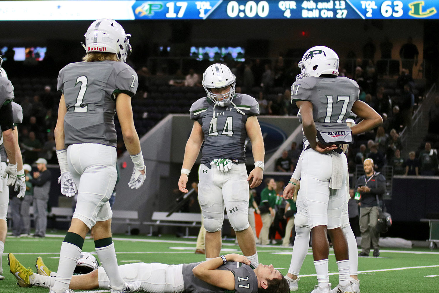 Senior kicker Cade York, No. 27, lays on the turf to reflect on his last football game as a Prosper Eagle. Fellow teammates Derien Ivy, No. 2, Aidan Sciano, No. 44, and Tyler Bailey, No. 17, gather around York. The Eagles fell 63-17 to the Longview Lobos Saturday night at The Star in Frisco.