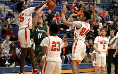 Point guard Josh Davis shoots the ball but is blocked by a McKinney North defender Jamien Hopkins, No.35.  Davis scored 11 points during the game. Prosper Eagles were unable to defeat the Bulldogs in their first game. The team will compete in their first tournament of the season Nov. 19-20 at Lone Star High School in Frisco.