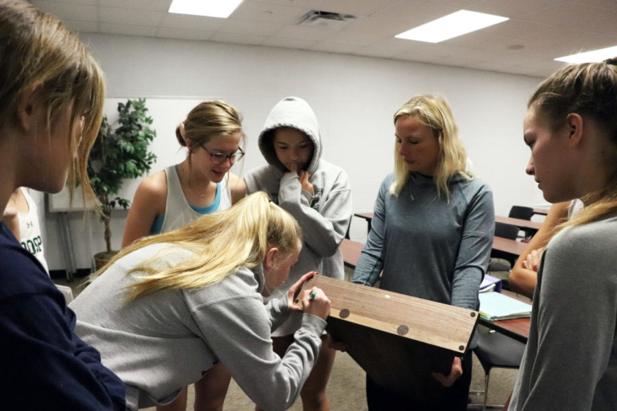 The cross country girls sign the state title trophy. They took third place at the meet on Nov. 3.