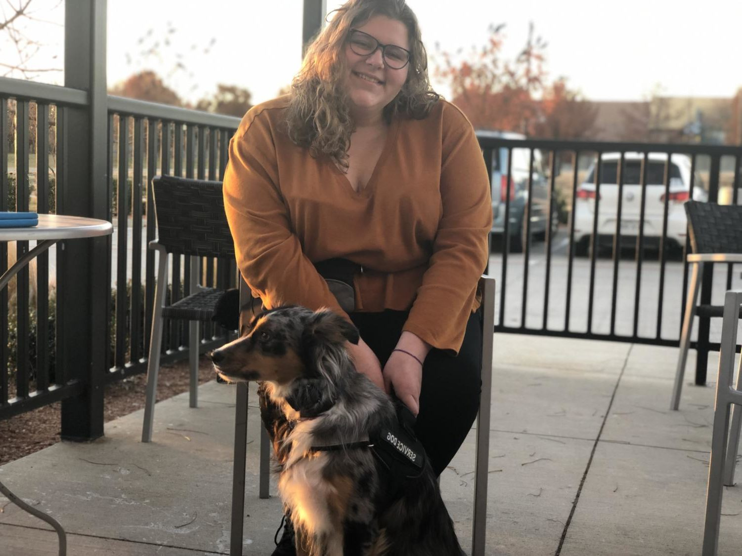 Student Jennifer Sieira sits with her service dog, Hero.  After a battle to bring him to campus, she is able to have him ready to assist her at all times.