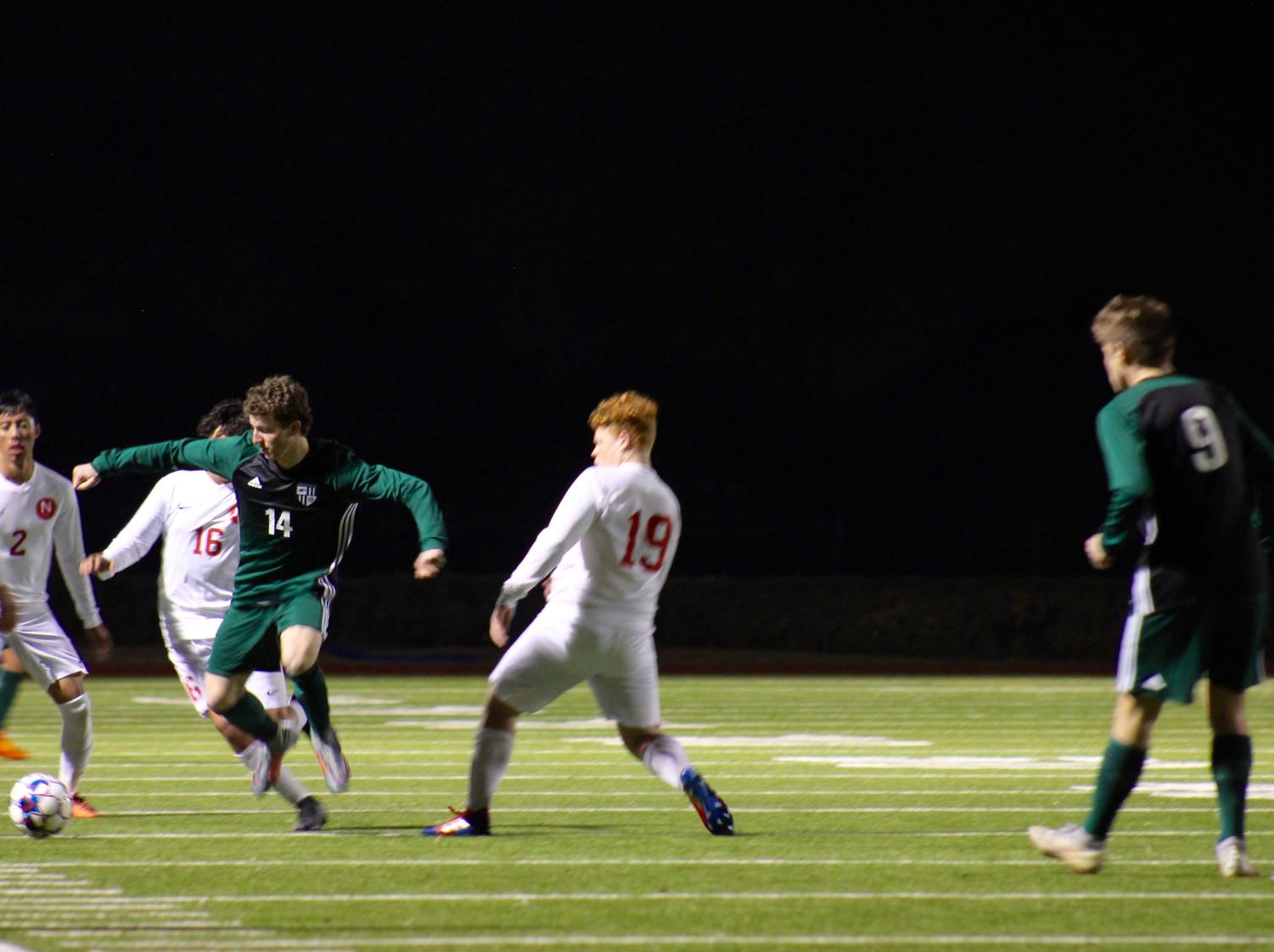 Senior Nolan DaRosa, No. 14, attempts to steal the ball from Justin Northwest players. The varsity boys soccer won 5-1 at their first home game Jan. 17. DaRosa scored the second goal in the first half.