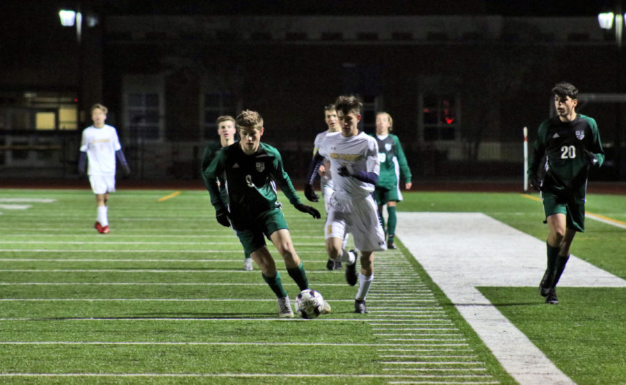 Junior Jack Simonini runs with the ball down the field in the varsity soccer game against McKinney. They played Tuesday, Jan. 22. The Eagles lost 3-0.