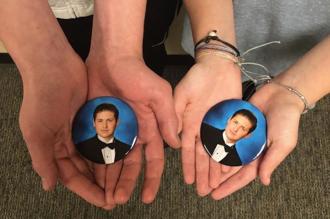 Braden Speed took his own life Oct. 30, 2018. Holding a button featuring Braden's yearbook photo are his voice team members Greg Valek and Courtney Yates.