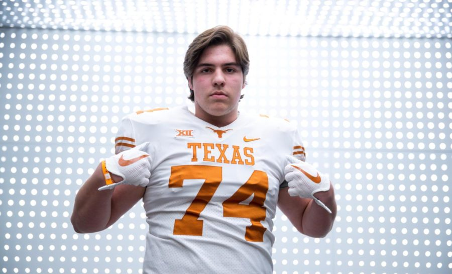 Offensive+tackle+Jake+Majors+puts+on+a+University+of+Texas+jersey.+He+committed+to+play+football+on+Jan.+24.+%E2%80%9CUT+was+calling+my+name%2C%E2%80%9D+Majors+said.+%E2%80%9CIn+my+heart%2C+I+knew+I+wanted+to+stay+in+Texas+and+be+a+Longhorn.%E2%80%9D