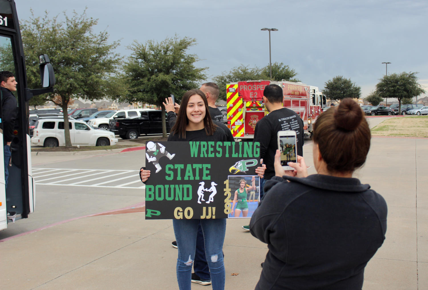 Junior Juliana (JJ) Baugher holds up a wrestling sign Friday, Feb. 22, before the team heads off to the UIL State Championship, held Saturday, Feb. 23. She placed fourth and sophomore John (LJ) Richardson placed sixth. The meet was held at the Berry Center in Cypress, Texas.