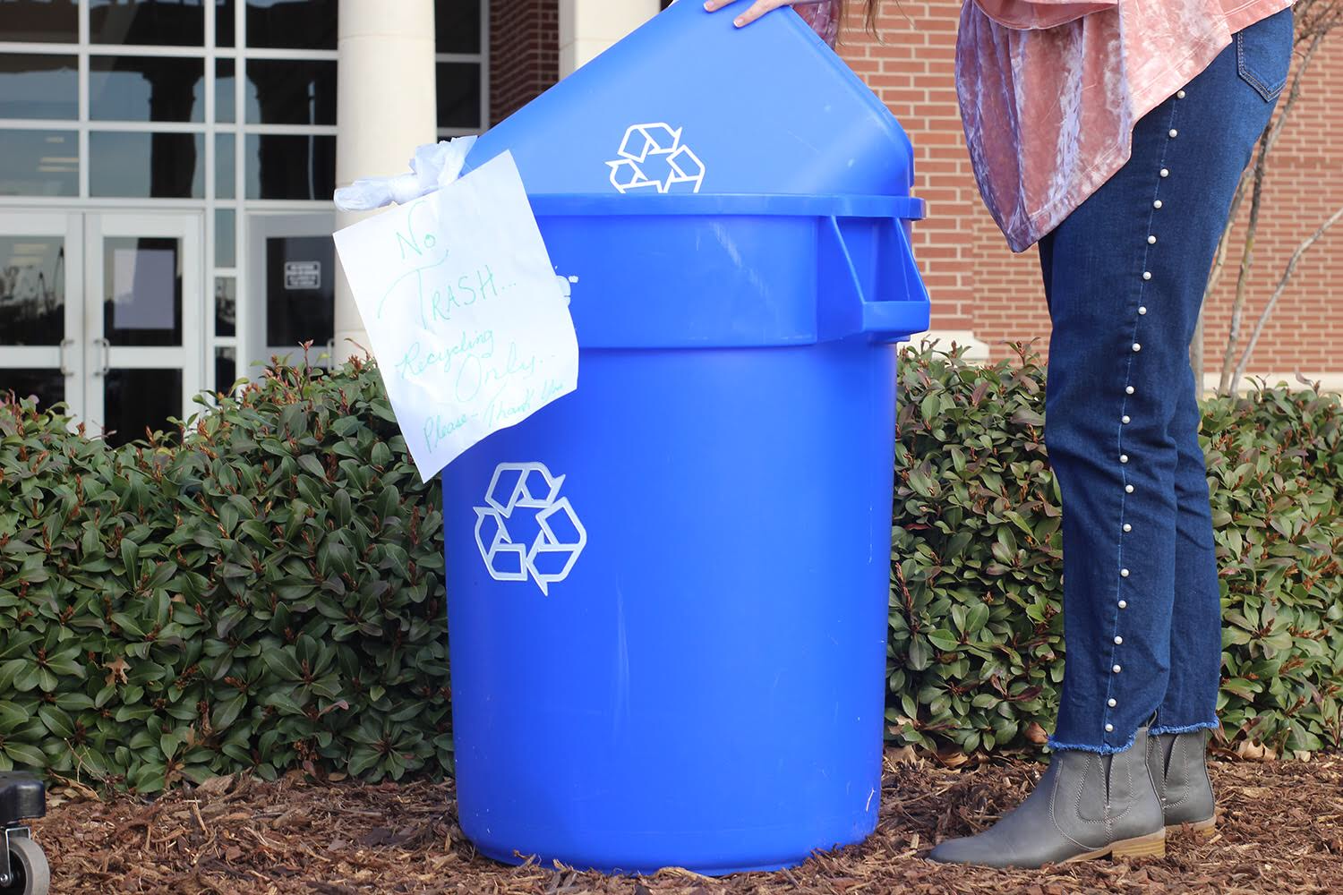 Sophomore Nikki Hansen collects recycling and puts it in a recycling bin labeled