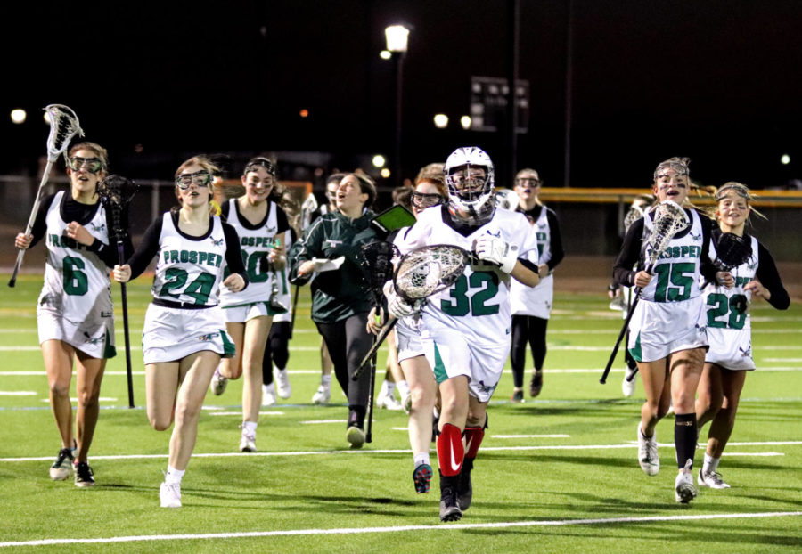 Goalkeeper Hope Raspberry, No. 32, rushes onto the field alongside her teammates at Frontier Park Feb. 25. The girls lacrosse team defeated Ursuline that night 9-3.