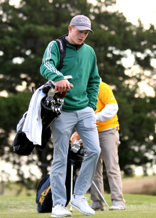 Jacob+Strong+carries+his+equipment+on+the+golf+course+at+the+Gentle+Creek+Country+Club.+Strong+and+other+golfers+showcased+their+skills+in+the+district+rounds+April+1-2.