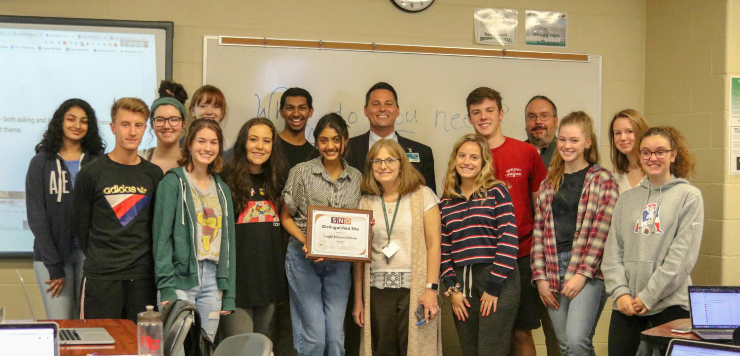 Principal John Burdett and assistant principal John  Boehringer present the Eagle Nation Online staff with their Student Newspapers Online  Distinguished Site plaque. Advised by Lisa Roskens, the staff has 17 published articles on