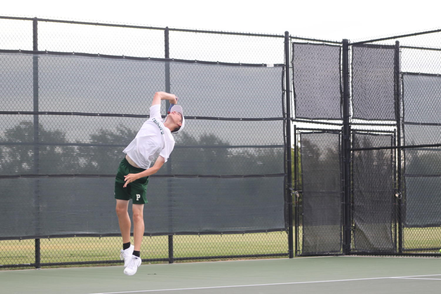 Junior varsity tennis player, Andrew Kochevar, serves the ball at McKinney North opponent.
