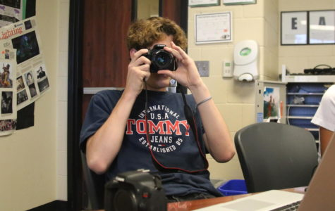 Luke McCann learns the basics of cameras in Mrs. Roskens' first-period Photojournalism I class. He struggled to find a battery that fits his camera since the staff took the rest of them for an event earlier that morning.
