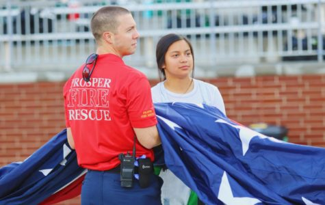 Spirit leader Alyssa Gonzalez and a Prosper first responder hold the American Flag as the National Anthem is sung. The choir joined athletes and coaches on the field last Friday, Aug. 30, to sing