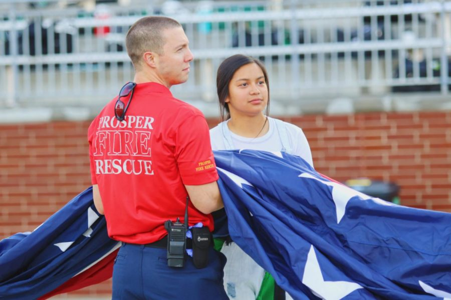 Spirit leader Alyssa Gonzalez and a Prosper first responder hold the American Flag as the National Anthem is sung. The choir joined athletes and coaches on the field last Friday, Aug. 30, to sing The Star-Spangled Banner. First responders, military members and veterans will be honored at the USA pep rally Friday, Aug. 6 starting at 2:30 p.m.