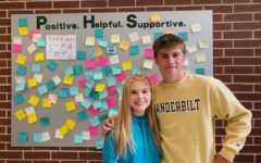 """Hope Squad members McKinley Bownds and Jack Simonini pause for a moment in front of the Kindness Wall. The students in this new program at the high school are in charge of keeping the board restocked with positive messages. Students can take an encouraging note whenever they need one, or they can pass by it. """"I feel that being on Hope Squad is really going to open my eyes,"""" sophomore  member Jordyn Leggiere said. """"It will make me happy by being able to help people, and to remind them that they aren't alone, and that they matter so much."""""""