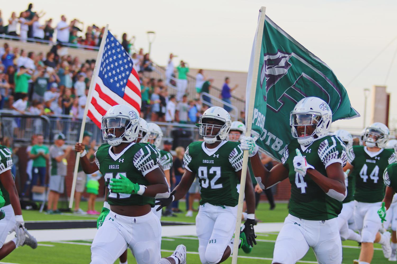 Sophomore Tyler Bailey, No. 4, runs out of the tunnel holding a Prosper flag with seniors J.T. Lane, No. 28, and Malachi Edwards, No. 92 alongside him. The Eagles beat Rowlett 31-7 in their first game of the season. They will play Keller Timber Creek Friday, Sept. 6 at the Children's Health Stadium.