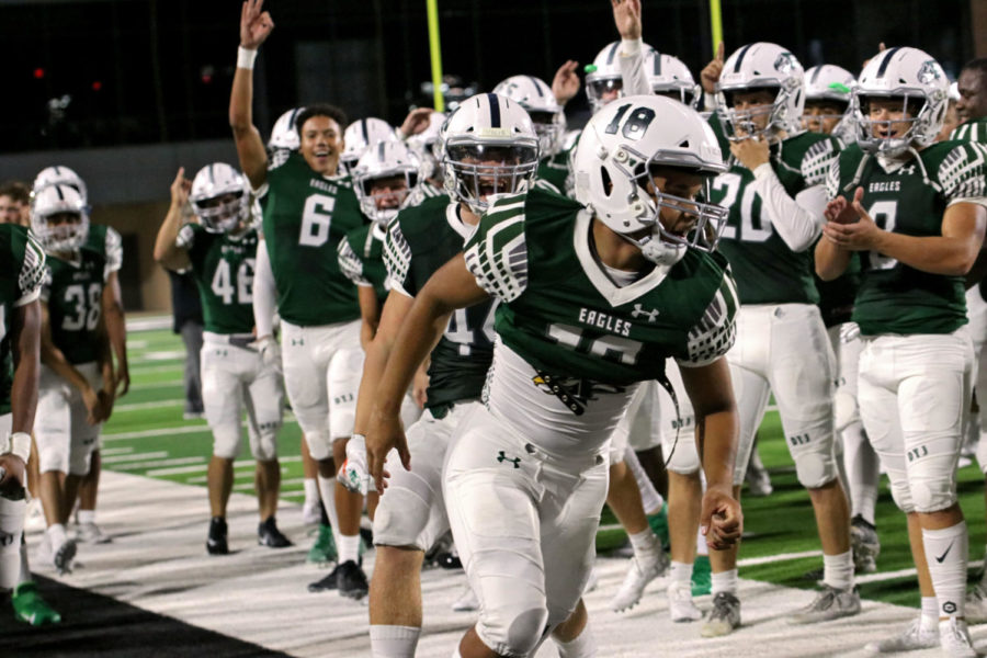 Junior Julian Huggins, No. 18, celebrates with his teammates after the Eagles win against Rowlett. The team dominated their first game at the new Children's Health Stadium. Huggins scored a touchdown in the fourth quarter.