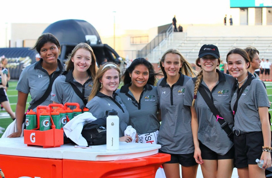 The student athletic trainers - senior Tasha Sayles, senior Ashlyn Wilkes, senior Kelly Cutler, senior Grammy Kornkanok Sophonsakulrat, junior Paige Benzick, junior Christian Folmar and sophomore Kylie York - stand and talk before the Sept. 27 varsity game against Plano East. In the attached column, sophomore athletic trainer and writer Kylie York covers the benefits of this program.