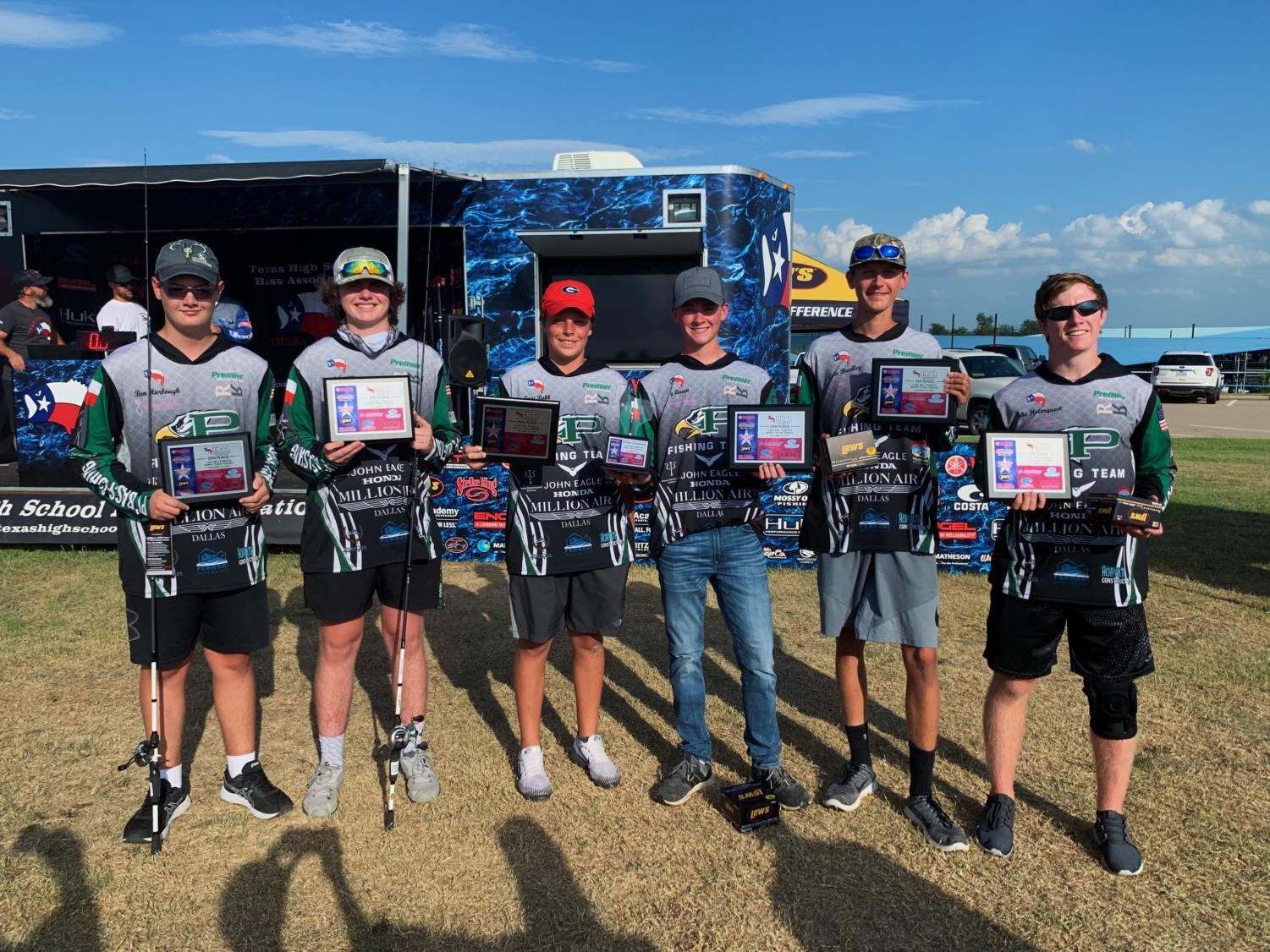 Members of the bass fishing team hold up awards after a tournament.