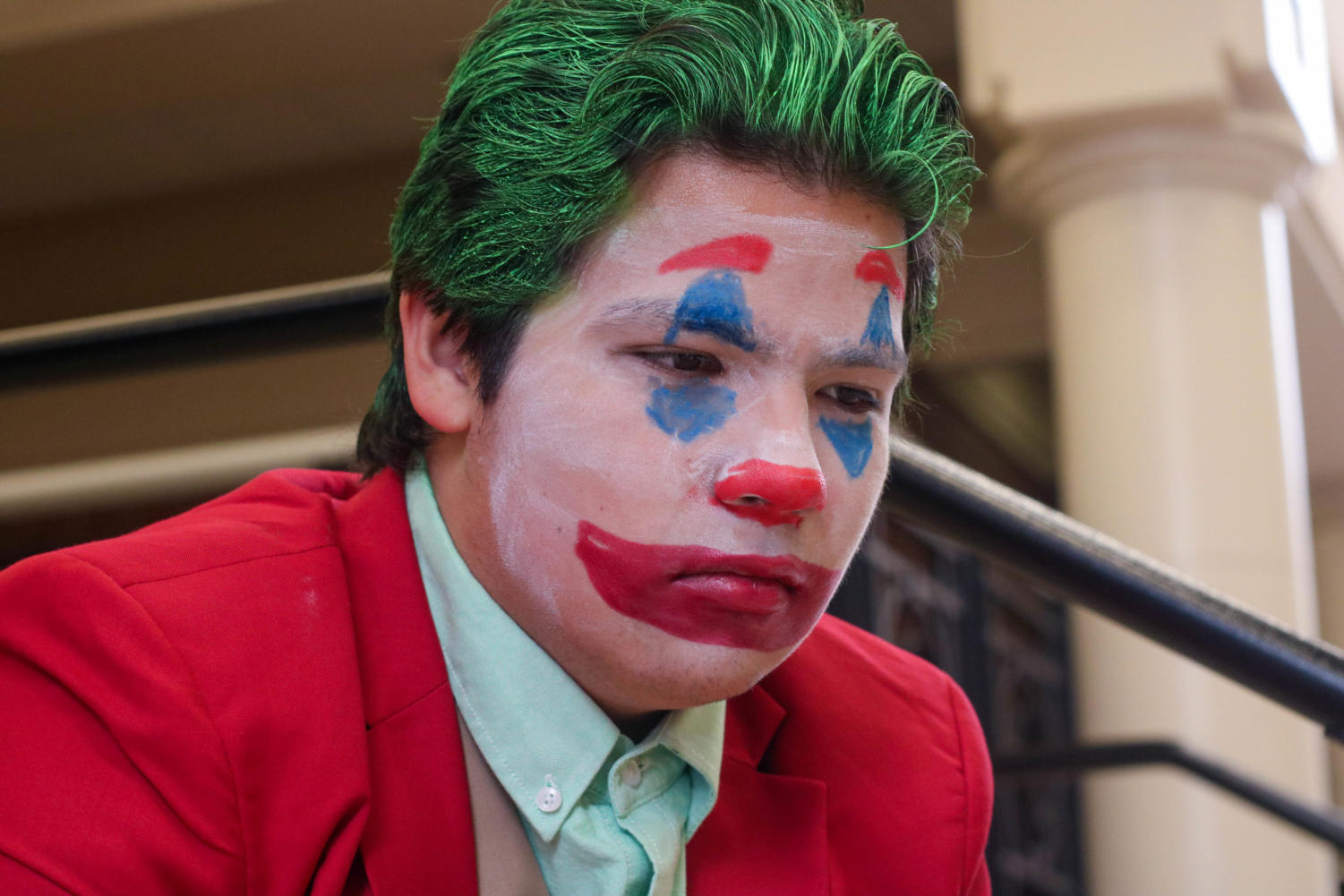 """Senior Erland Merwin poses in his joker costume on the steps to the Auditorium. """"We live in a society,"""" Merwin said, quoting one of the Joker's most famous and meme-ified lines. In this column, writer Maddie Moats highlights the many reasons for which she claims the Halloween spirit has died."""
