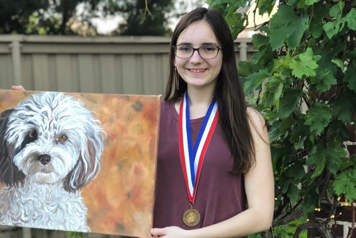 Senior Sophia Giasolli, donned with a medal won at the VASE state, holds her prize painting.