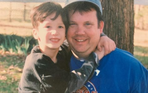 Government teacher Rodney McCall sits with his son. This picture hangs on the bulletin board in McCall's classroom.