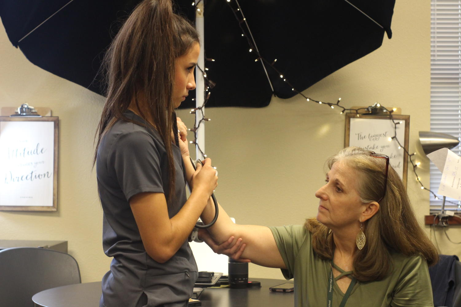 """Junior Natalie Smathers checks journalism teacher Lisa Roskens' pulse. Smathers participates in the Health Science career track offered here. She said she hopes to continue in the same field for her career. """"I've always wanted to be in the medical field,"""" Smathers said. """"I've always loved taking care of people and making them feel good, so it was something I would naturally be good at."""""""