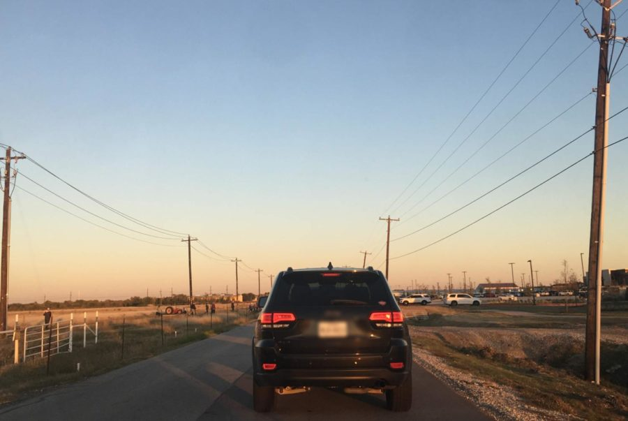 People+on+the+far+left+walk+across+the+fields+from+Boyer+Elementary+and+try+to+weave+between+cars+to+cross+West+Frontier+Parkway.+The+vehicles+sit+in+traffic+as+they+wait+for+police+officers+to+let+them+into+Children%27s+Health+Stadium+at+Prosper+parking+lots.++No+crosswalk+or+additional+lighting+is+available+for+the+students+and+community+members+who+must+cross+this+roadway+to+return+to+the+designated+student+pick-up+area+at+Boyer.