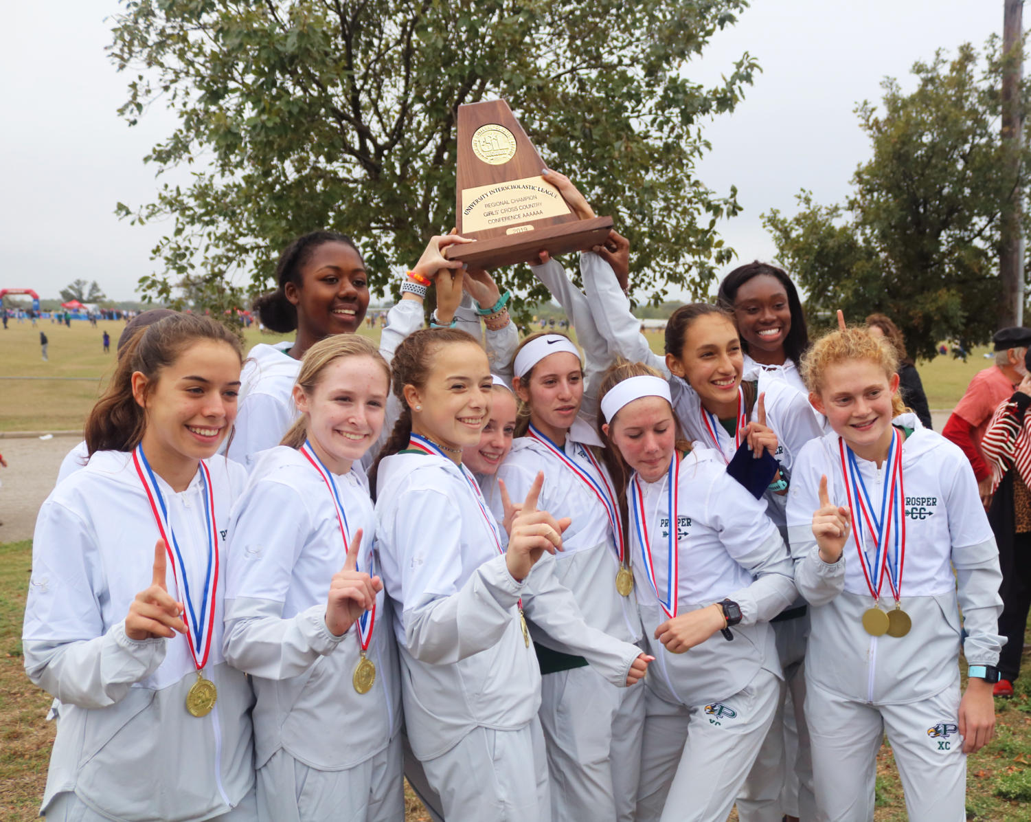 The girls varsity team holds up their first place regional trophy following the meet on Oct. 26.