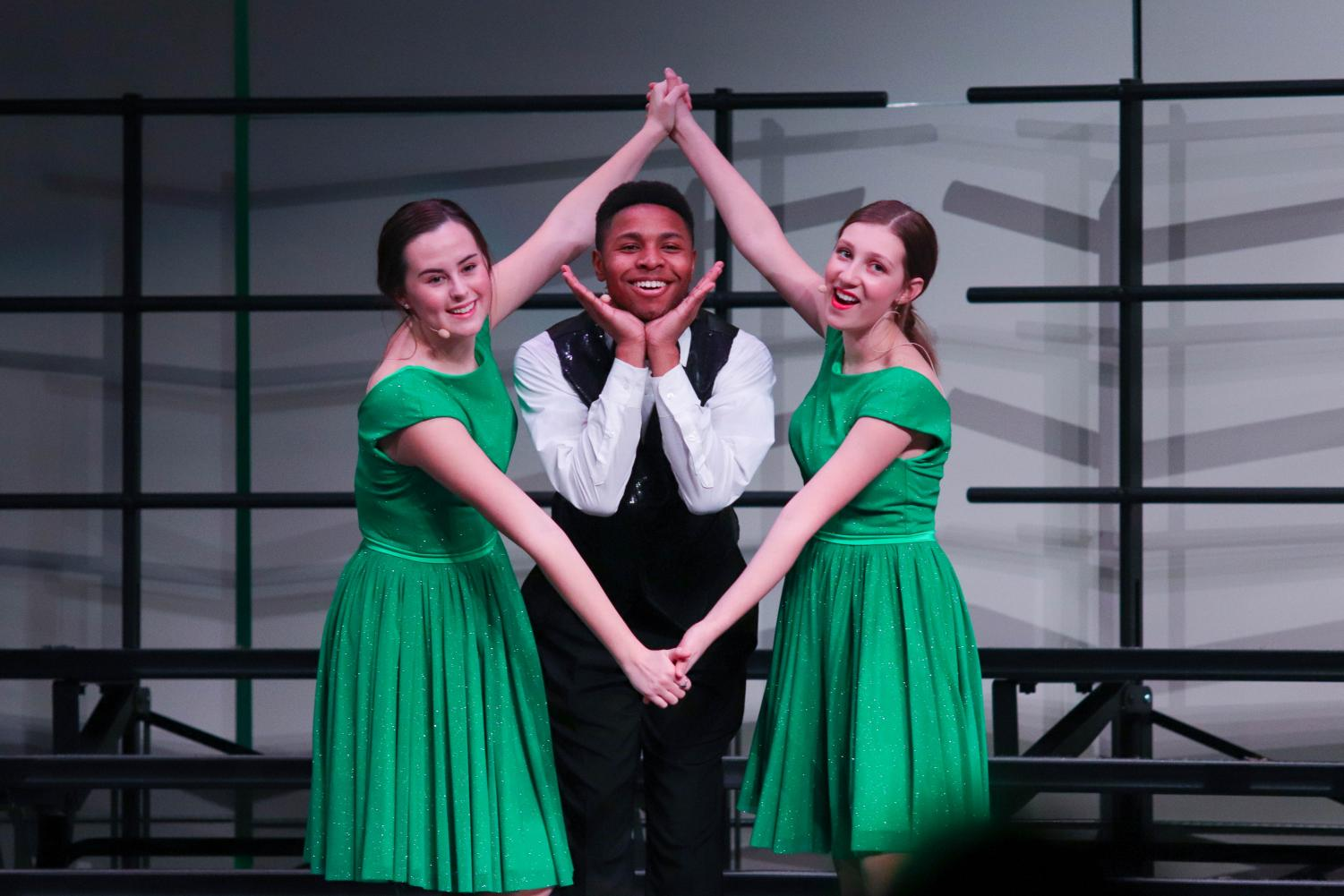 "Sophomore Ella Heflin, senior Micah Mohead and sophomore Sarah Wyatt posed in the finale of their performance. The show choir simultaneously rendered a choreographed performance and sang under the direction of Crystal Chamberlain. ""It was an amazing experience,"