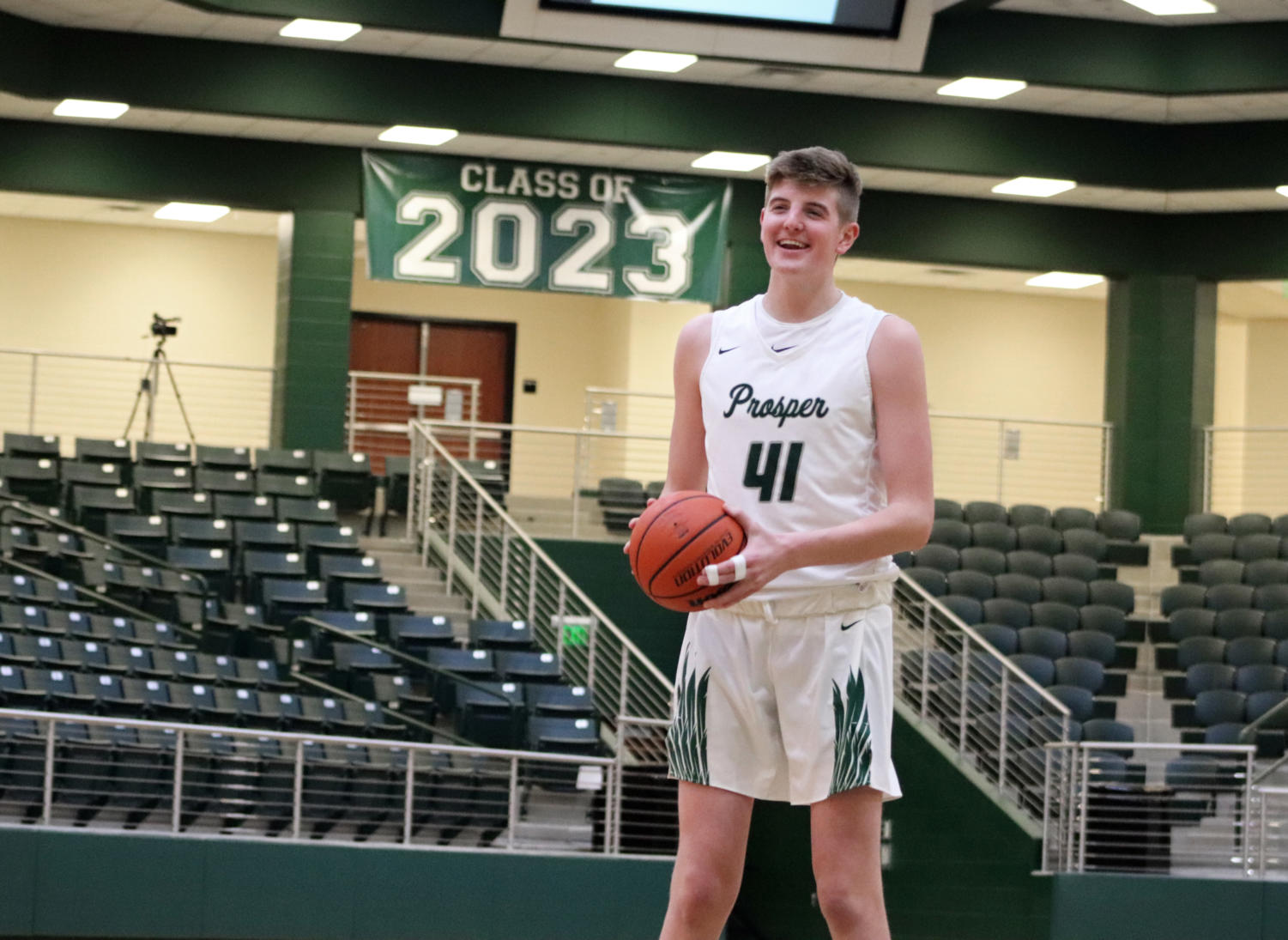 Smiling at his teammates, Conner Kern, No. 41, takes some shots before second half. Kern got multiple rebounds and put up a few points to bring the Eagles to victory against the Rams. The varsity Eagles play on Dec. 5-7 in the PISD Classic.