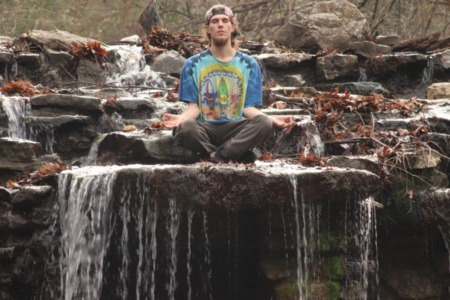 """Environmental enthusiast and self-proclaimed hippie Matthew Addic listens to the harmonious sounds of birds mixed with the pacifying sounds of water flowing into the stream below. Addic said he sits and lets all of the negative energy flow out of him through the practice of meditation. """"Its better than any music Ill ever hear,"""" Addic said."""