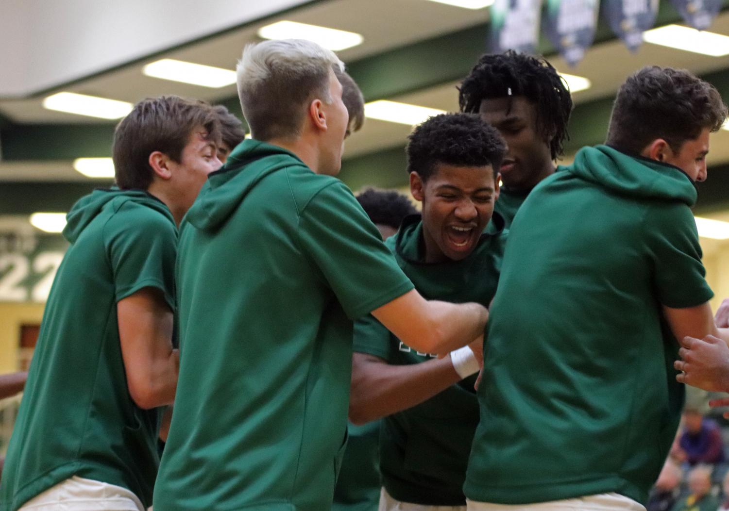As the team warms up, junior Jaythan Jackson, in the center, gathers with teammates before the game. The varsity Eagles faced the Plano West Wolves Friday, Jan. 10. They came off with a close win 64-60.