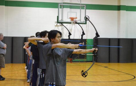 During the beginning of the third round at 10 meters, junior Ethan Doucet aims and draws his arrow in an effort to score a bullseye. Archery team member and photojournalist Julia John captured this moment Tuesday, Feb. 25.