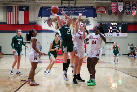 Despite being blocked and having the attention of three guards, sophomore Peyton Mosley goes in for a lay up. Mosley missed the shot, but she made up for it when she made both free throws. Her shots helped the Eagles win 48-35 against the Broncos.