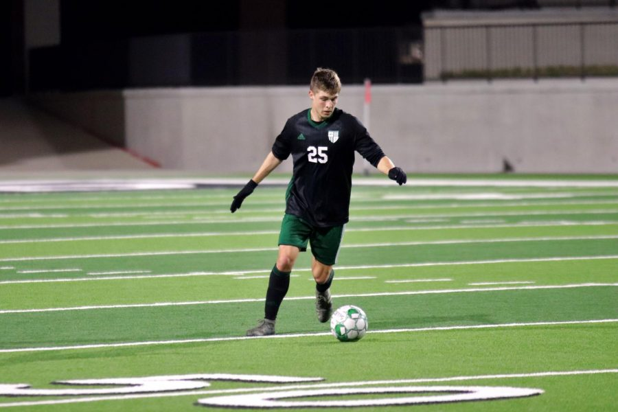 Center-back Cole Newman, No. 25, looks down before sending the ball forward. The Eagles were tied with McKinney High for third place in district standings, but beat the Lions 3-1.