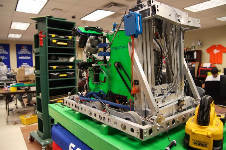 A robot sits atop a table in the robotics room. The robots created by the robotics team are programmed to shoot objects and hang from bars. The purpose of the event is to build a robot that can shoot power cells or medium sized balls into a powerport to get points, Wood said.