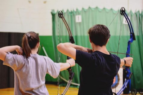 "Sophomore Jessica Hampton and Freshman Sean Rich, set up their shots and aim for their targets. Both archery teams practice two nights a week in preparation for upcoming tournaments. ""I like how it is a sport anyone can do,"" Hampton said."
