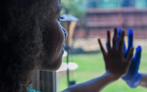 Nine-year old London-Olevia Brown cries as she presses her hand to the gloved hand of her adult sister, Itzy Hernandez, against a window. Social distancing is a necessary measure that many countries have undertaken to slow the spread of the coronavirus. But what will its long term effects be, aside from flattening the curve? Columnist Kate L. Keeler examines the possible outcomes of humans being left without humans.