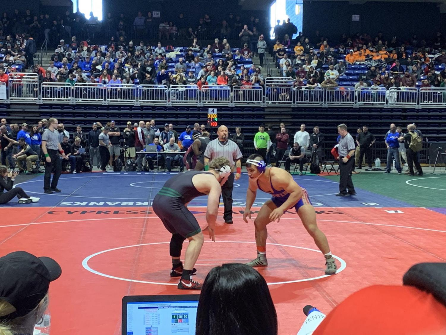 """Senior Rylan Bonds wrestles his opponent during the competition for the state champion title. Bonds wrestles in the 220-pound weight class. """"My motivation was to just come back and prove I could be there,"""" Bonds said. """"Even though I had gotten hurt, I could still wrestle. When I won state, it felt like it was a dream almost, it took me a couple of days to realize I actually won."""""""