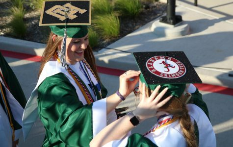 Senior girls adjust their graduation caps before walking to their seats. These students spirited their future colleges with a touch of glitter. These members of the Top 10 percent of the  class of 2020 received the honor of graduating first.