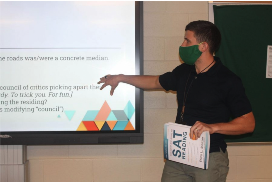 In front of his board in Room 1217, Leith McMillan covers subject-verb agreement while holding an